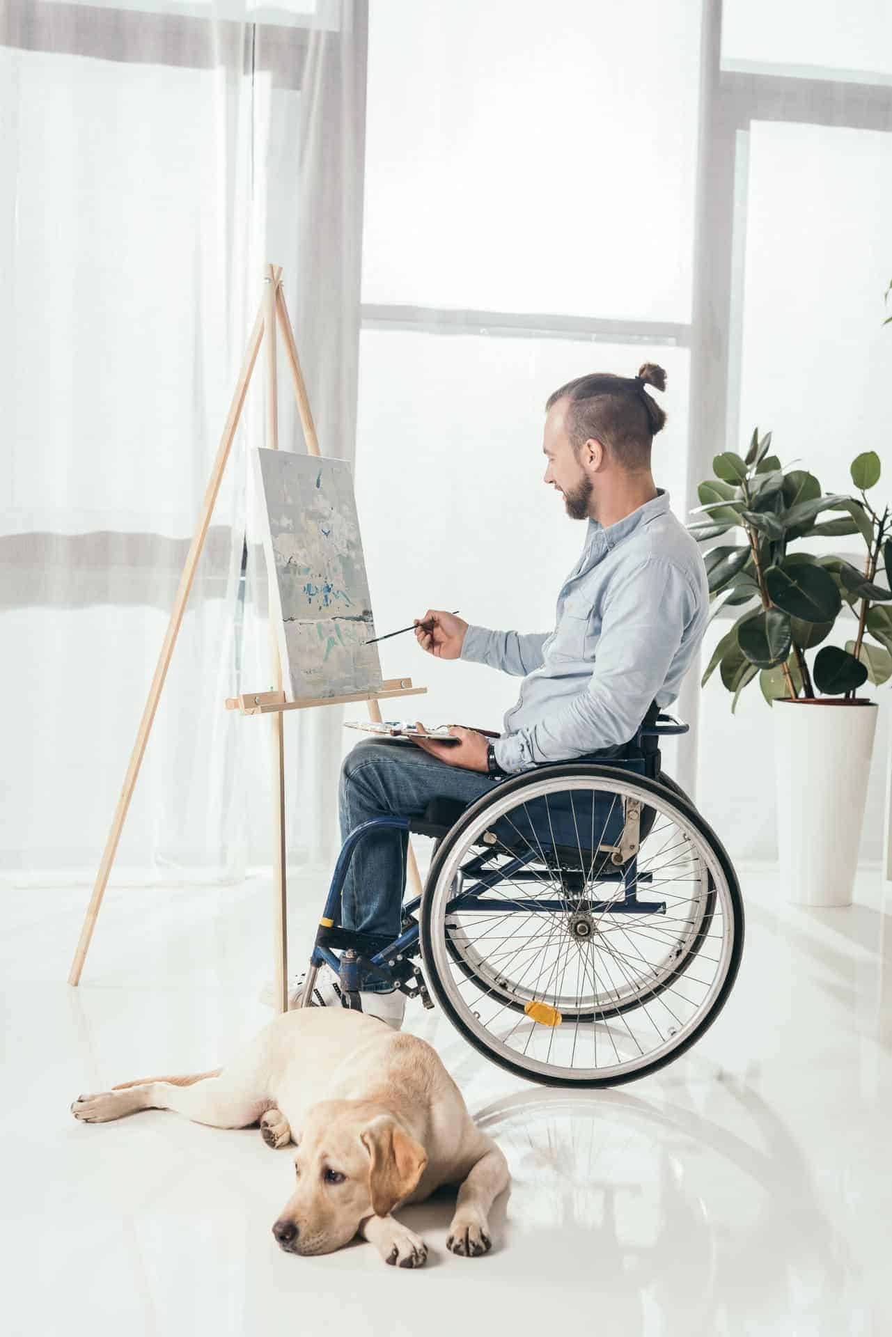 Man in wheelchair painting in Art Therapy Class in Glasgow's Centre for Integrative Care